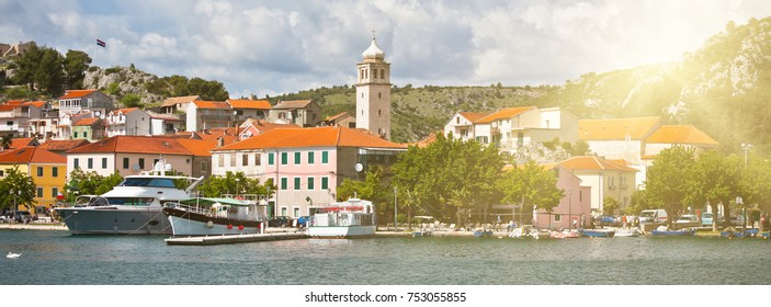 Skradin is a small historic town and harbour on the Adriatic coast in Croatia. Long wide banner with solar effect