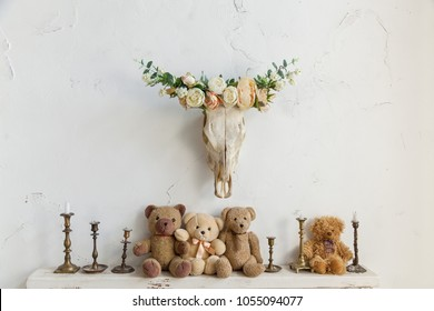 the skull of an animal on the wall is decorated with flowers, on the shelves sit toy bears and candlesticks with candles
