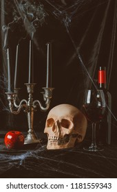 skull, apple, red wine and candelabrum with smoky candles on black cloth with spider web