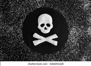 Skull and bones made from sugar and a scattering of granulated sugar on a black background. concept - greater consumption of sugar kills.