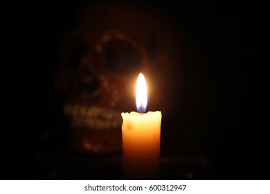 Skull and candle. Black magic. Focus on candle. Halloween.