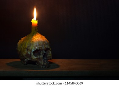 Skull with candle on head which has candlelight on the wooden plank in dark room / Still life image and space for texts
