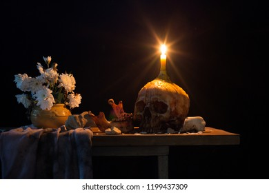 Skull with candle on head which has candlelight  and vase withered flower on the plank in dark room / Still life image and space for texts