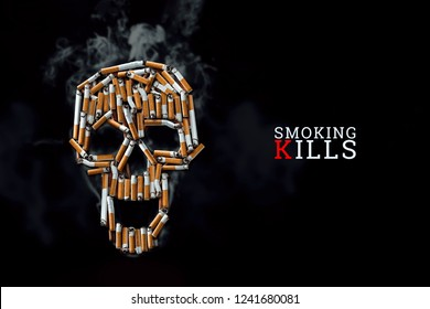 Skull from cigarettes, butts, on a black background. The inscription smoking kills. Creative background. The concept of smoking kills, nicatine poisons, cancer from smoking, stop smoking. Copy space.