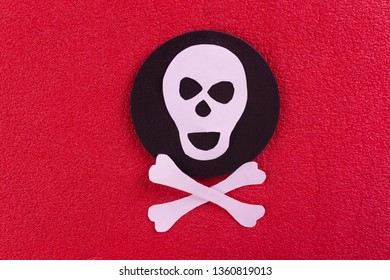 skull and crossbones made of paper. red background