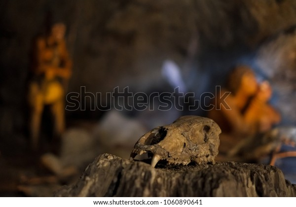 Skull of a dog with teeth. In the background, ancient people