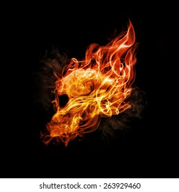 Skull in flame on dark background.