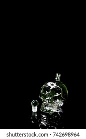 Skull glass bottle on the black reflective surface plate