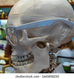 Skull with Glasses. Chemistry or medical laboratory safety concept with skull wearing plastic lab goggles, safety glasses are used to protect the eyes.