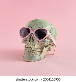 Skull with glasses on pink background. Halloween creative fashio