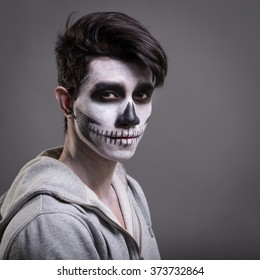 Skull make up portrait of young man in studio. Grey background.