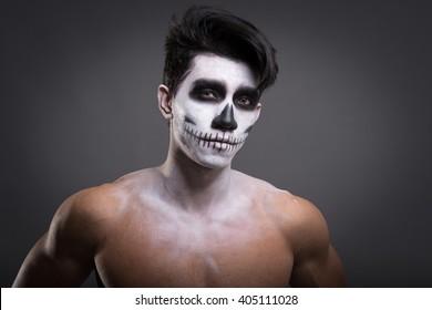Skull make up portrait of young man torso in studio.