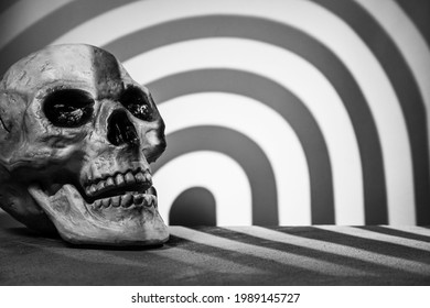 Skull on a gray background with a podium and abstract blurred light stripes in the shape of an arch. Selective focus. Space for lettering, design, and presentation.