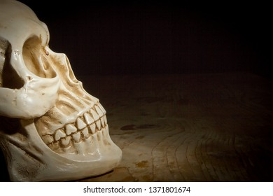 Skull on old wooden table on black background