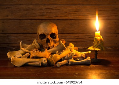 Skull on pile bone with candle light on wooden table  / Still life style and selective focus, image red tone from candle light