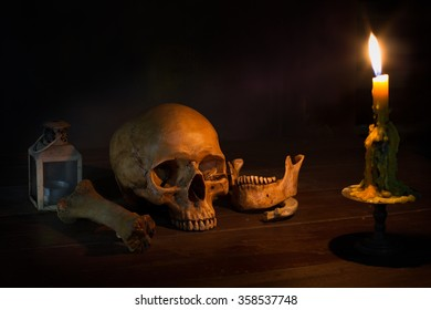 Skull, pile of bone, and candle, on wooden table / Still life style