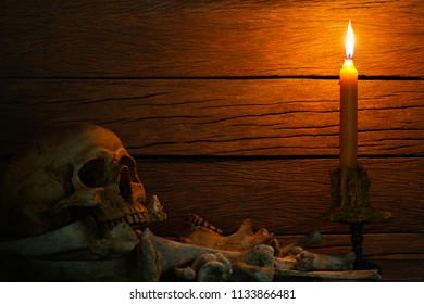 Skull and pile of bones with candle and candle light, put on the glass and wooden wall background / blurred and selective focus, Still Life Image