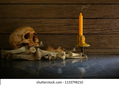 Skull and pile of bones with candle put on the glass and wooden wall background / blurred and selective focus, Still Life Image