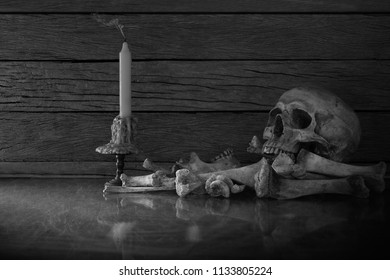 Skull and pile of bones with candle put on the glass and wooden wall background / adjustment color black and white for background selective focus, Still Life Image