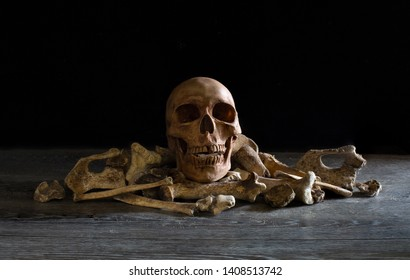 Skull and pile of bones put on wooden table and black background / Selective focus, Still Life Image and space for texts
