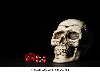 Skull and red dice on black background