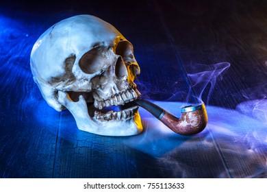 The skull smokes a pipe. Skull in tobacco smoke.