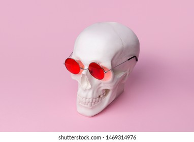 Skull in sunglasses on pastel pink background. Halloween costume party concept