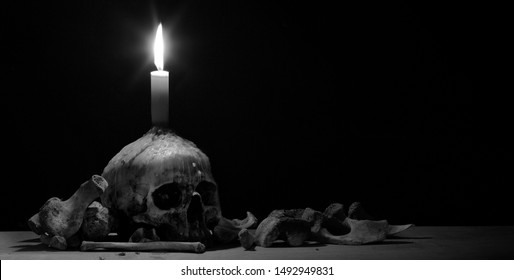 Skull which has candle on head and lighting from candle and pile of bone on wooden plank in dark light room / selective focus space for text and adjustment size and color black and white for banner, c