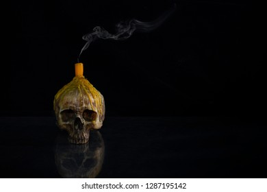 Skull which has extinguished candle on head and put on the mirror and dark background  / Still life image and space for texts