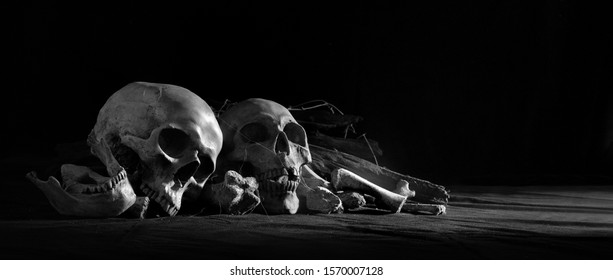 Skulls with pile bone front dark background and on black cloth floor / Still life image, blurred and select focus, space for text, adjustment size and color for banner, cover, header