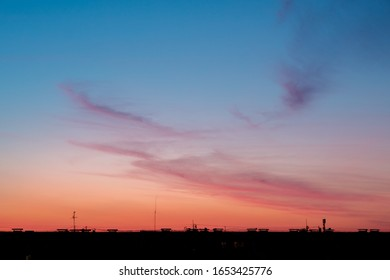 sky after sunset with a smeared cloud below the line of a multi-story building with antennas. evening summer sky blue to red gradient