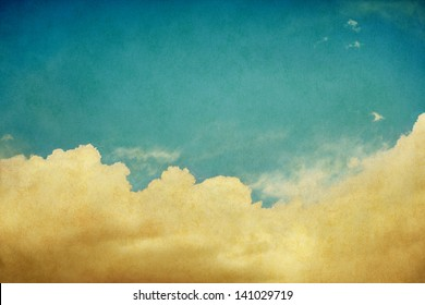 Sky and billowing clouds on a textured background with vintage colors.  Image displays a pleasing paper grain and texture when viewed at 100 percent.