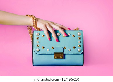Sky blue handbag purse and beautiful woman hand with red manicure isolated on pink background.