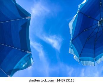Sky and blue umbrellas on the beach