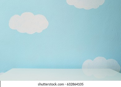 sky blue wall and an empty table.