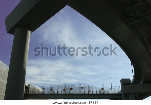 sky bridge framed by freeway ramp under blue sky and white clouds