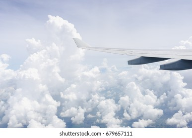 Sky and Cloud View through an airplane window with plane wing visible.