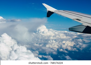 Sky and clouds with airplane wing, view from airplane
