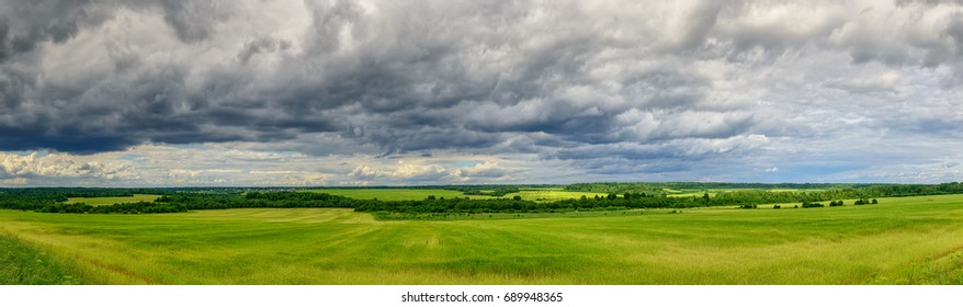 Sky with clouds over a green field. Panorama