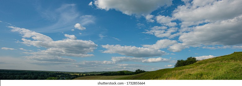 Sky and clouds over a meadow on a hillside on a sunny day. Summer season. Web banner. Ukraine. Europe.