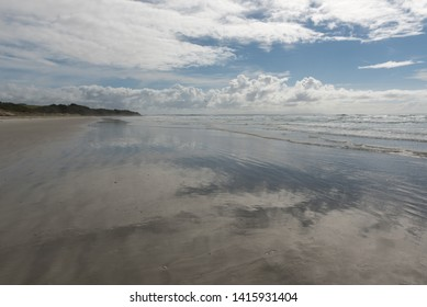 The sky and clouds reflected in the wet sands of the beach at Karikari Moana, Northland, New Zealand.