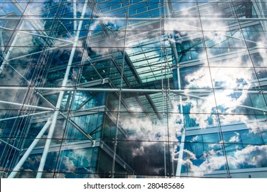 Sky and clouds reflected in the windows of an ecological and sustainable building.