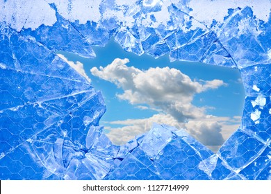 A sky with clouds seen through a broken glass - freedom concept image