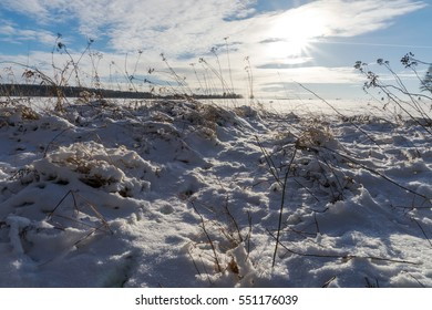 Sky with clouds and sun over the snowy field