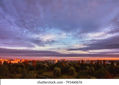 Sky with clouds at sunrise over morning city.