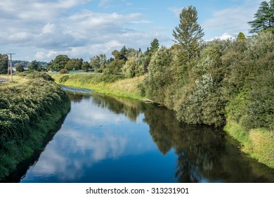The sky, clouds and trees are reflected in the Green River in Kent, Washington.