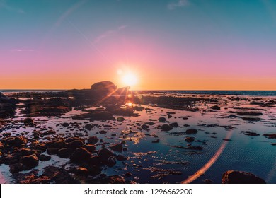 The sky colored in light hues of oranges, pinks and baby blues as the sun sets over the pacific ocean horizon, reflecting the colors at low tide and casting rock formed silhouettes.