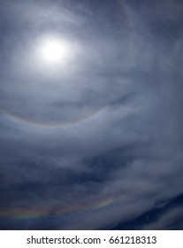 sky covered with light clouds, full circular halo around the sun, partial second halo