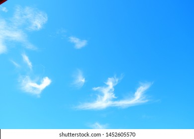 Sky in the daytime, on a clear day, and a thin white cloud drifting along the wind.