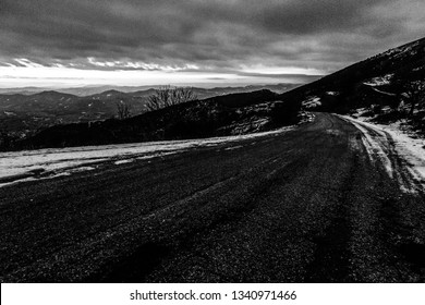 sky at dusk, with mountains layers and a road in the foreground